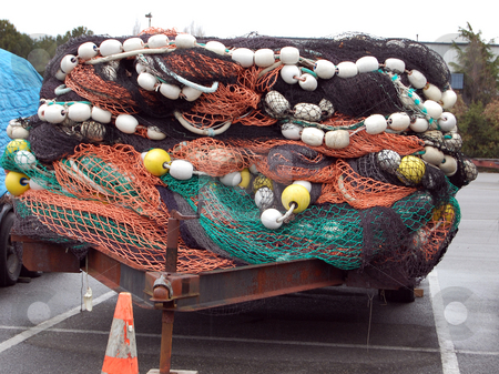 Trailer Loaded With Buoys and Fishing Nets stock photo, A trailer is loaded with colored buoys of yellow and white, with black and orange fishing nets. by Valerie Garner