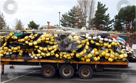 Buoys and Nets on a Truck Trailer stock photo, Yellow and white colored buoys and fishing nets are loaded onto a truck trailer. by Valerie Garner
