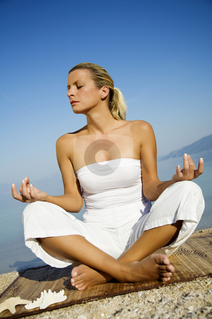 Zen stock photo, Young female meditating on the beach by Liv Friis-Larsen