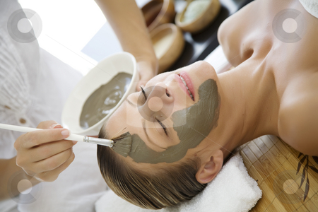 Mud mask stock photo, Professional applyinh mud mask to female client by Liv Friis-Larsen
