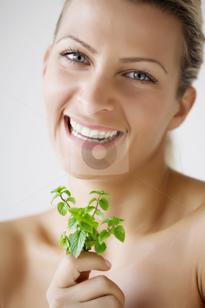 Female with fresh herbs stock photo, Woman holding peppermint sprig by Liv Friis-Larsen
