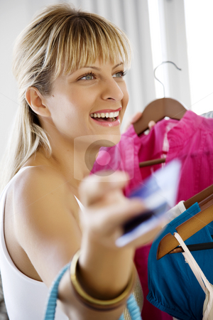Shopping with credit card stock photo, Young woman clothes-shopping with credit card by Liv Friis-Larsen