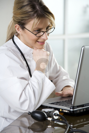 Female doctor in her office stock photo, Doctor at her desk by Liv Friis-Larsen