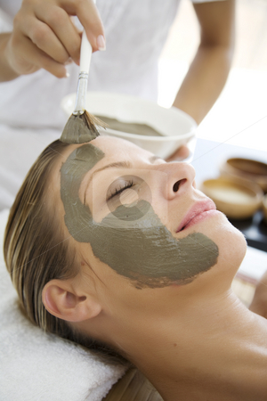 Mud mask stock photo, Woman havin mud mask applied to her face by professional by Liv Friis-Larsen