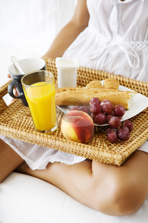 Delicious breakfast stock photo, Female with breakfast tray in her lap by Liv Friis-Larsen