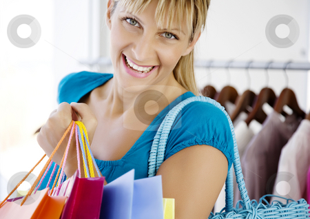 Out shopping stock photo, Young woman in store with shopping bags by Liv Friis-Larsen