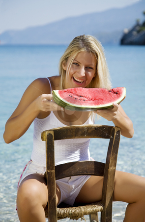 Eating water melon stock photo, Young happy female eating water melon on the beach, sitting on a classic mediterranean chair by Liv Friis-Larsen