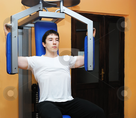 Man in gym stock photo, Young bodybuilder in a gym at workout. by Ivan Paunovic