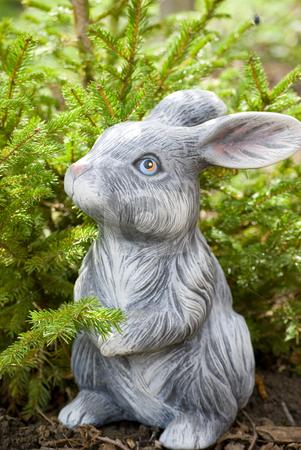 Rabbit statue stock photo, Rabbit statue on green pine tree backgound by Desislava Dimitrova