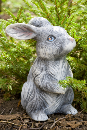 Rabbit statue stock photo, Rabbit statue on green pine tree backgound by Desislava Dimitrova