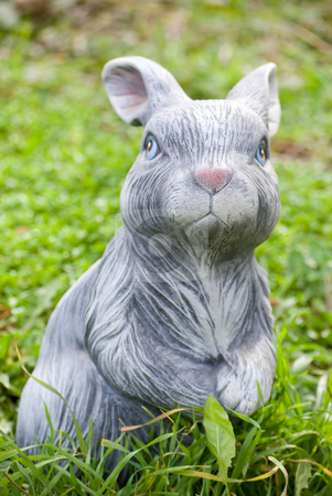 Rabbit statue stock photo, Rabbit statue on green grass backgound by Desislava Dimitrova