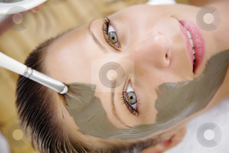 Mud mask stock photo, Young woman is having a mudmask applied to her face by Liv Friis-Larsen
