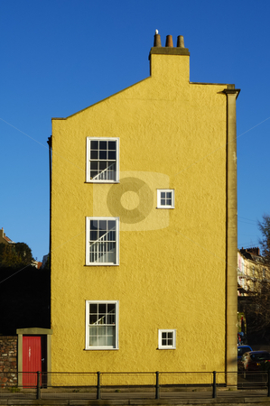 Yellow house stock photo, The end of a row of terraced houses with red door and white bird on chimney pot. by Alistair Scott