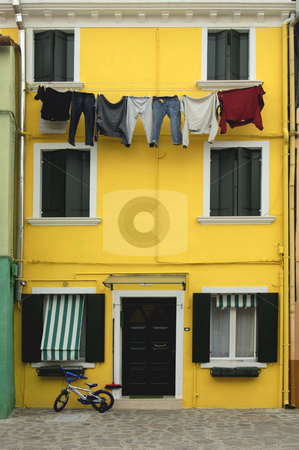 Domestic view stock photo, A house in Murano, one of the Venetian islands, with washing hanging on a line, a broom by the door and a child's bicycle. by Alistair Scott