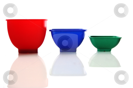 Measuring cups stock photo, Measuring cups in bright primary colors. Isolated on white by Martin Darley