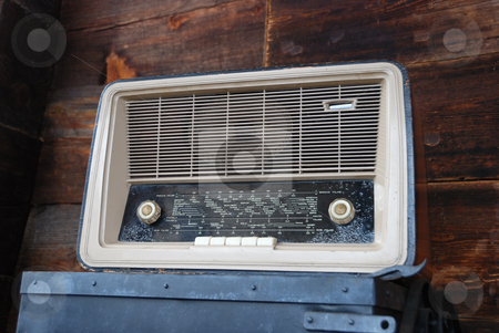 Vintage Radio stock photo, Vintage radio standing on a steel box with wooden wall in background. by Denis Radovanovic