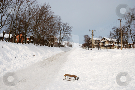 Hill Road in Winter stock photo, Hill road covered with snow going between two rows of houses with old sled left in foreground. by Denis Radovanovic