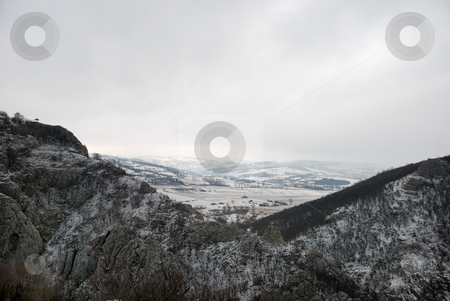 Valley in Winter stock photo, View from above between two hills at a snow covered valley with overcast sky. by Denis Radovanovic