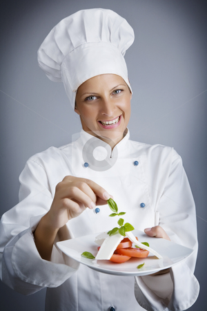 Adding the herbs stock photo, Portrait of female chef, composing a cheese and tomato starter by Liv Friis-Larsen