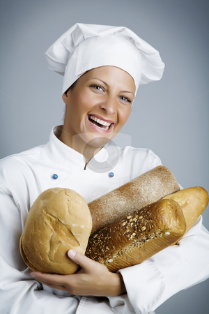Happy baker stock photo, Female baker with hands full of bread by Liv Friis-Larsen