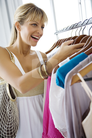 Clothes shopping stock photo, Young happy woman in clothes store by Liv Friis-Larsen
