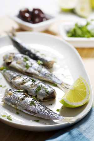 Grilled sardines stock photo, Grilled sardines with olives, lemon and parsley by Liv Friis-Larsen
