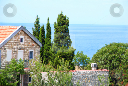 House on seaside stock photo, Stone house with red tiled roof between cypresses by adriatic sea by Julija Sapic