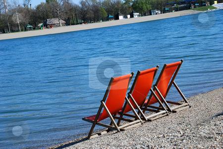 Orange folding chairs stock photo, Three orange folding chairs by blue water by Julija Sapic