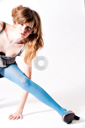 Teenager in blue pantyhose and grey blouse stretching stock photo, Studio portrait of a cute teenager by Frenk and Danielle Kaufmann