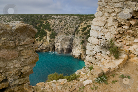 Hole in fort wall stock photo, A hole in an old fort wall, overlooking an aqua-marine body of water in the Algarve, near Sagres, Portugal. by Kevin Woodrow
