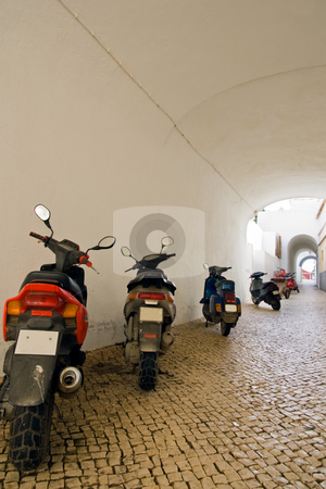 Motorbike line-up stock photo, A line-up of motorcycles along a tunnelled Portuguese street. by Kevin Woodrow