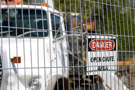 Construction Truck behind cage stock photo, A construction truck shot behind steel fencing, with a danger sign affixed. by Kevin Woodrow