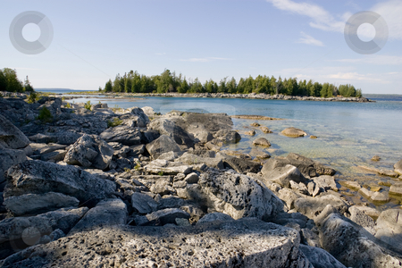 Rocky Beach with Island View stock photo, A rocky beach, clear water, clear day, and view of a small island in the distance. by Kevin Woodrow