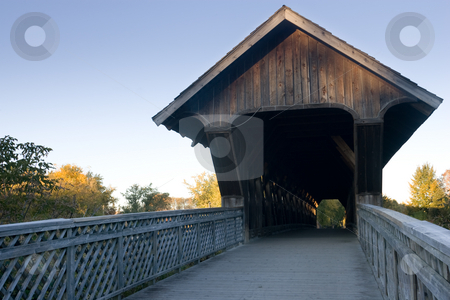 Covered walking bridge - front view stock photo, A view of the covered walking bridge, located in Guelph, Ontario, Canada, withe a blue sky background, and surrounding fall colours. by Kevin Woodrow