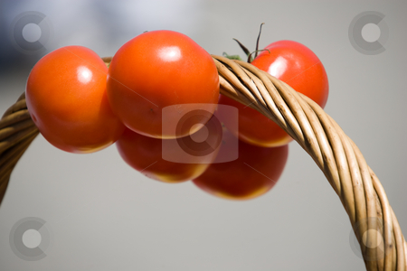 Tomatoe on basket handle stock photo, A bunch of tomatoes, hanging from the handle of a basket. by Kevin Woodrow