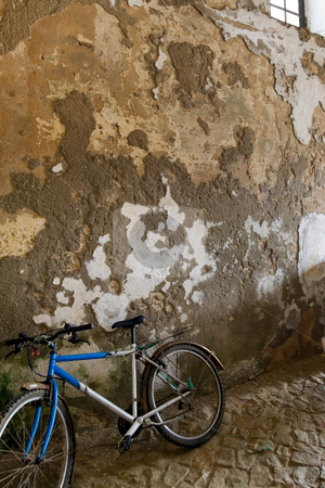Old bike against wall stock photo, An old bike up against an old textured wall. by Kevin Woodrow