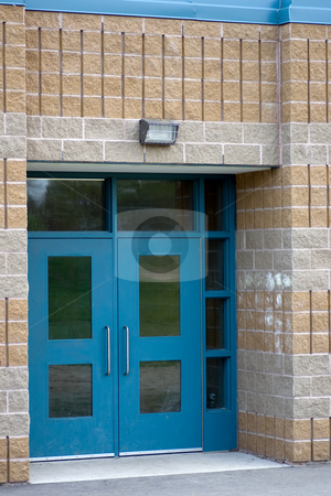 School doors stock photo, A set of blue school double doors surrounded by grey and brown brick. by Kevin Woodrow
