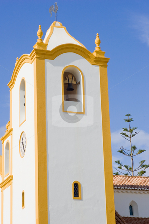 Vibrant church - Vertical stock photo, A vibrant church, white with yellow accents, set against a deep blue sky. by Kevin Woodrow