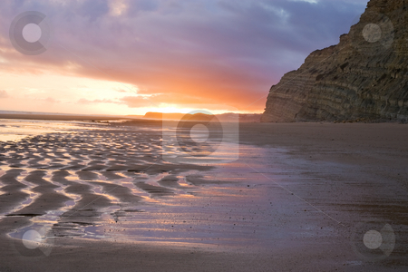 Sunset reflection on Sand stock photo, A sunset on the beaches of Lagos, Portugal, with reflections off of the outgoing tide, with cliffs in the distance. by Kevin Woodrow