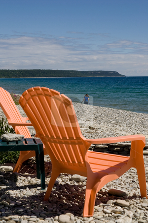 Relax and enjoy the view stock photo, A set of two orange deck chairs with a rocky beach background, low cloud cover, and blue sky. by Kevin Woodrow