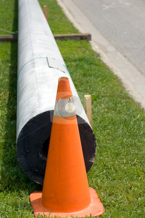 Hydro Pole Replacement stock photo, A new hydro pole waiting to be installed, stored by the side of the road on the grass. by Kevin Woodrow