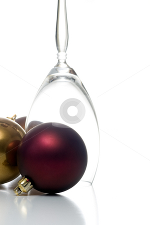 Christmas ornament series stock photo, Single upside down champagne glass surrounded by christmas ornaments, isolated on white. by Kevin Woodrow