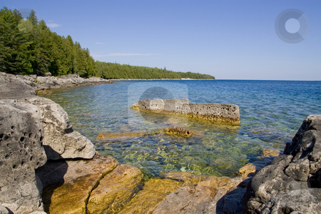 Rocky Cove stock photo, Tranquil water in a Rocky Cove on a Clear day, with sharp focus on the rock textures. by Kevin Woodrow