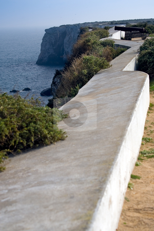 Fire at the invaders stock photo, Along the fort walls, focus on a cannon midway, with steep cliffs in the distance.  Fortaleza de Sagres, Sagres, Portugal by Kevin Woodrow
