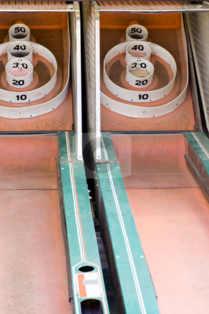 Skeeball game at amusement park stock photo, 2 lanes of a skeeball game from a traveling amusement company. by Kevin Woodrow