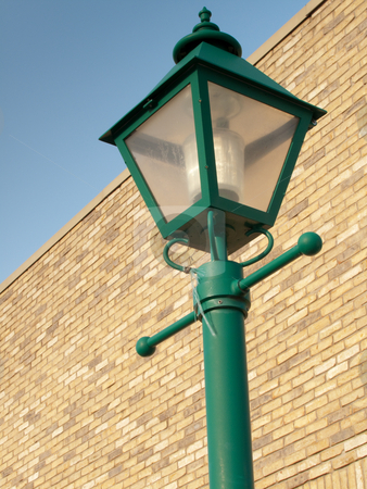 Lamp Post on brick stock photo, Top of a green lamp post, with a brick wall and blue sky in the background. by Kevin Woodrow