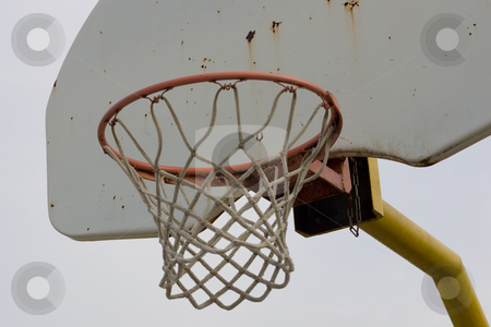 Basketball net and backboard, closeup stock photo, A closeup view of an old baketball net and backboard, isolated against a blue sky. by Kevin Woodrow