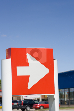 White arrow sign stock photo, Directional sign in front of retail stores, with blue sky background. by Kevin Woodrow