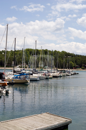 Summer at the marina stock photo, A foreground pier with a lineup of sail boats and sky in the background. by Kevin Woodrow