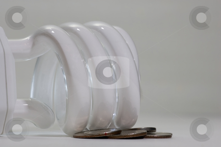 Saving money with new lighting stock photo, A compact fluorescent bulb, lying on its side with some american quarters, dimes and nickels scattered around it. by Kevin Woodrow